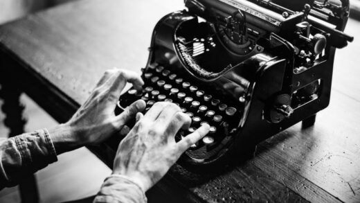 a black and white image of an old pair of hands typing on a typewriter